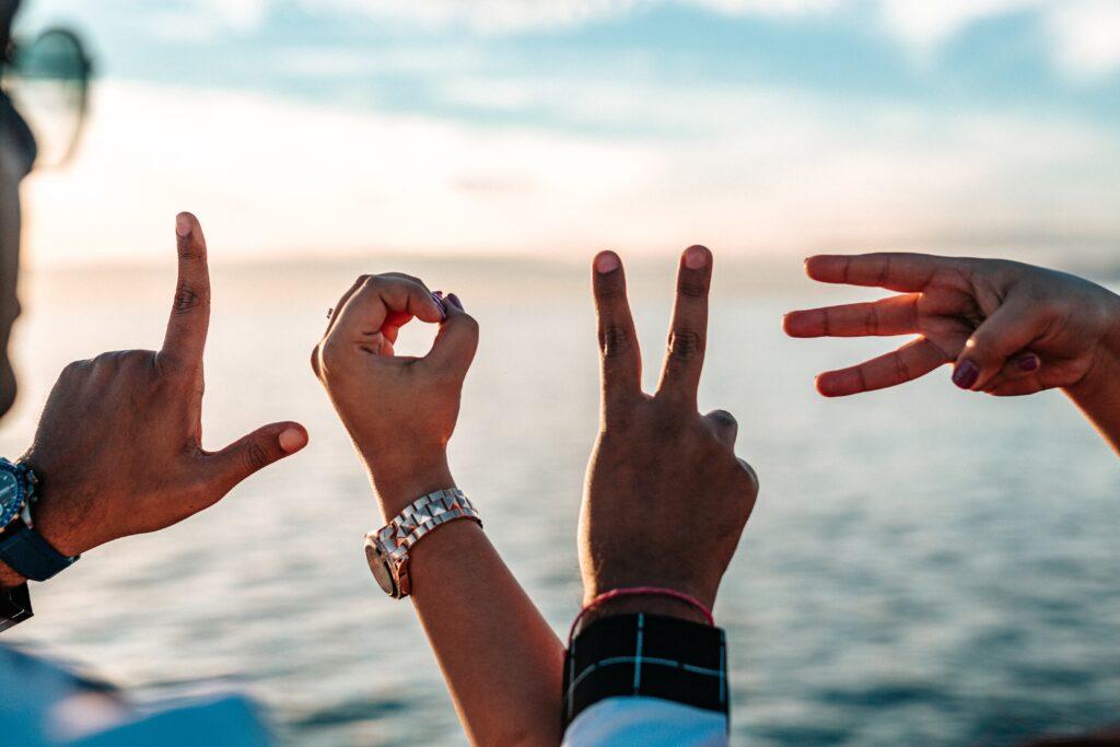 mani formano la scritta LOVE con il mare come sfondo