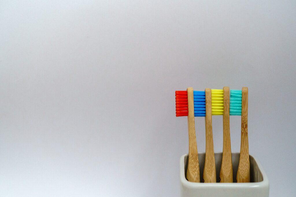 Tre spazzolini in bamboo in porta spazzolino su sfondo bianco e con setole colorate in rosso, blu, giallo, verde acqua.