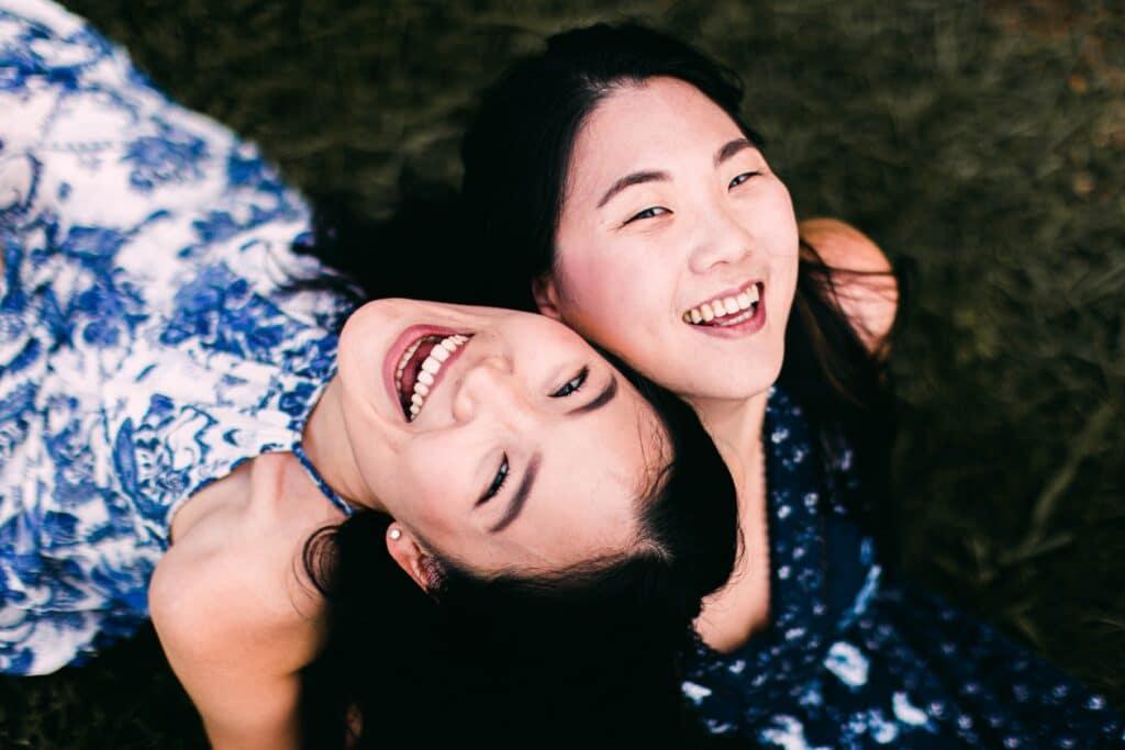 Due ragazze ridono su un prato mostrando denti bianchi.